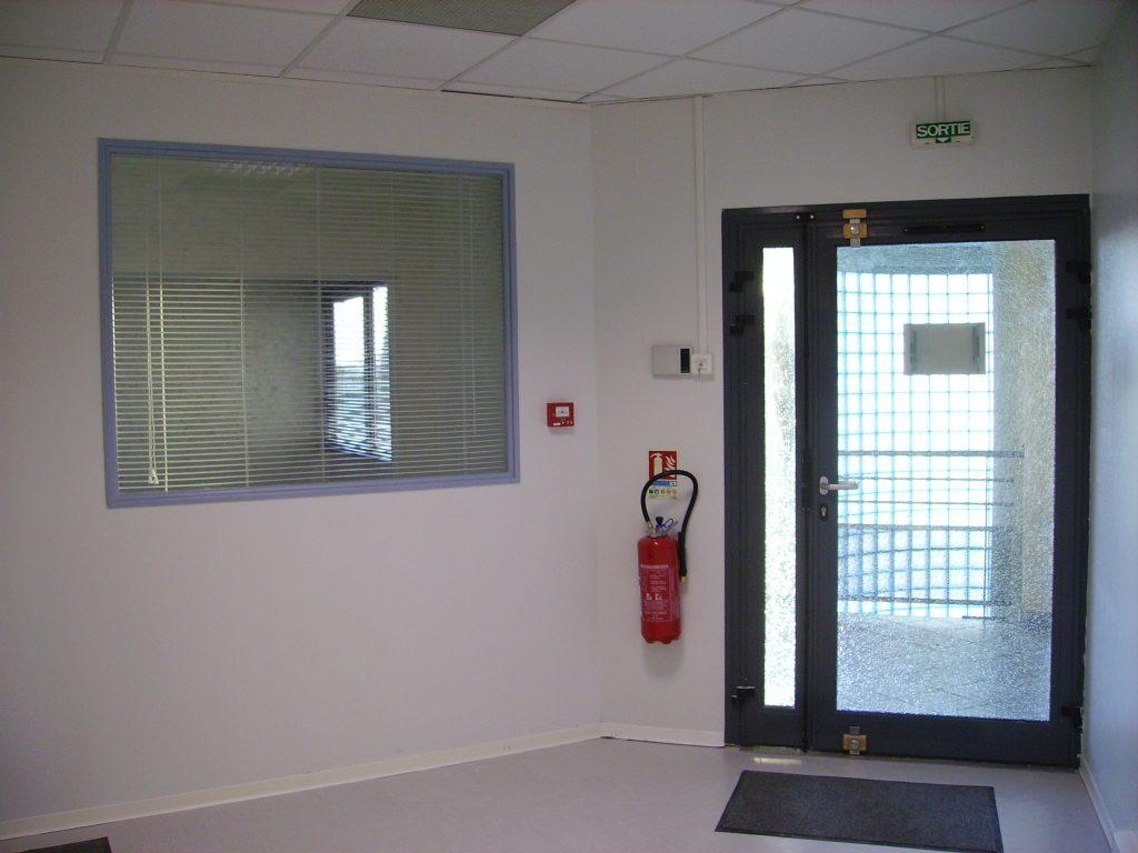 Couloir d'entrér d'immeubme avec une porte vitrée