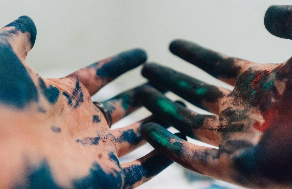 Mains avec de la peinture bleue, vert,noir et rouge sur les doigts