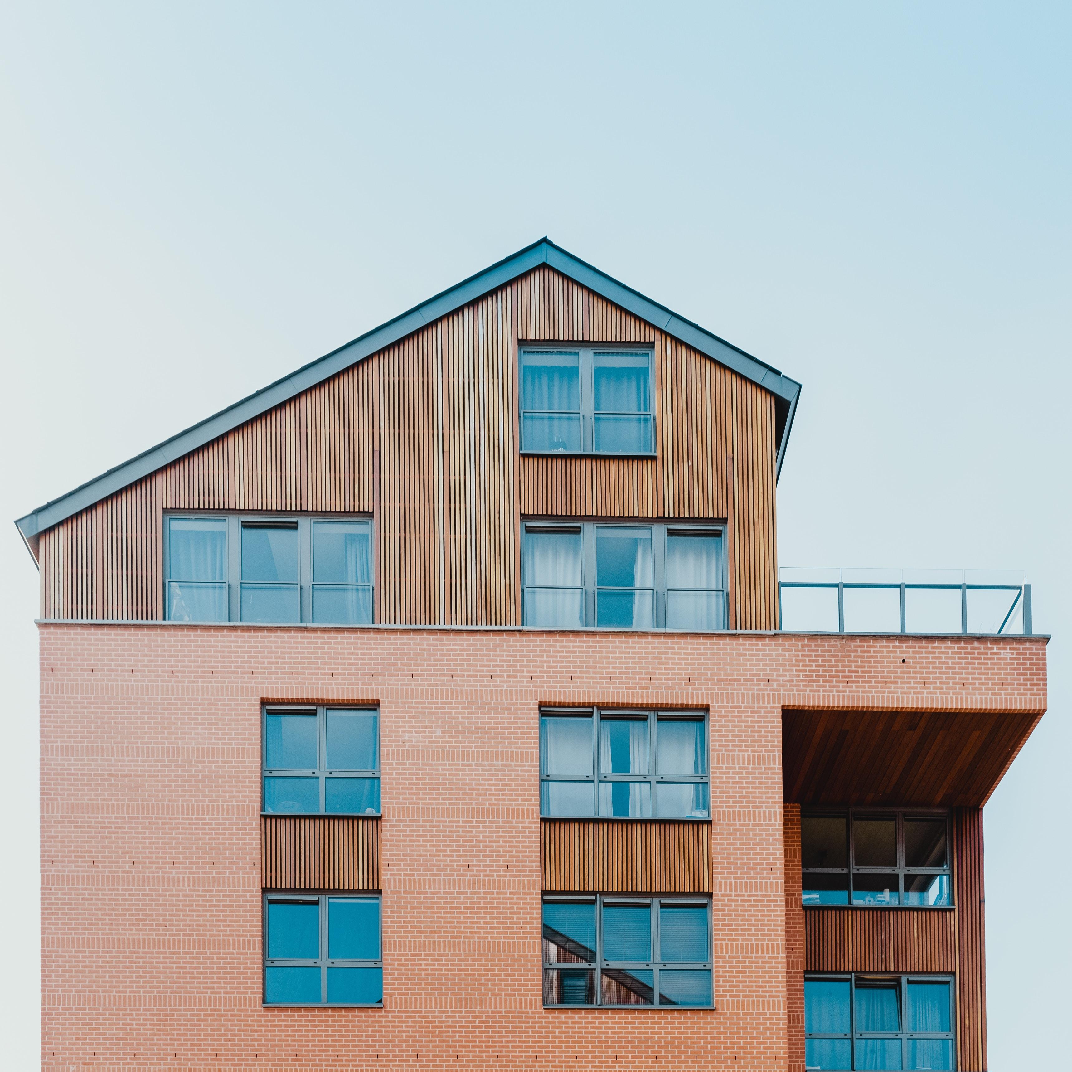 grande maison en bois à plusieurs étage et en briquette de parement