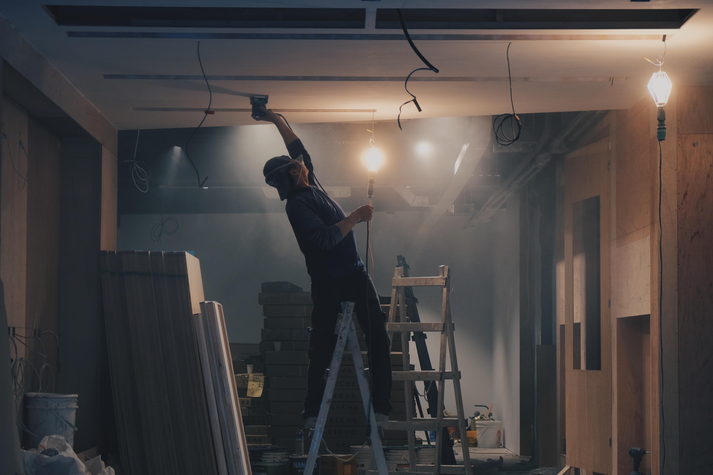 ouvrier sur une échelle en plein travaux de rénovation