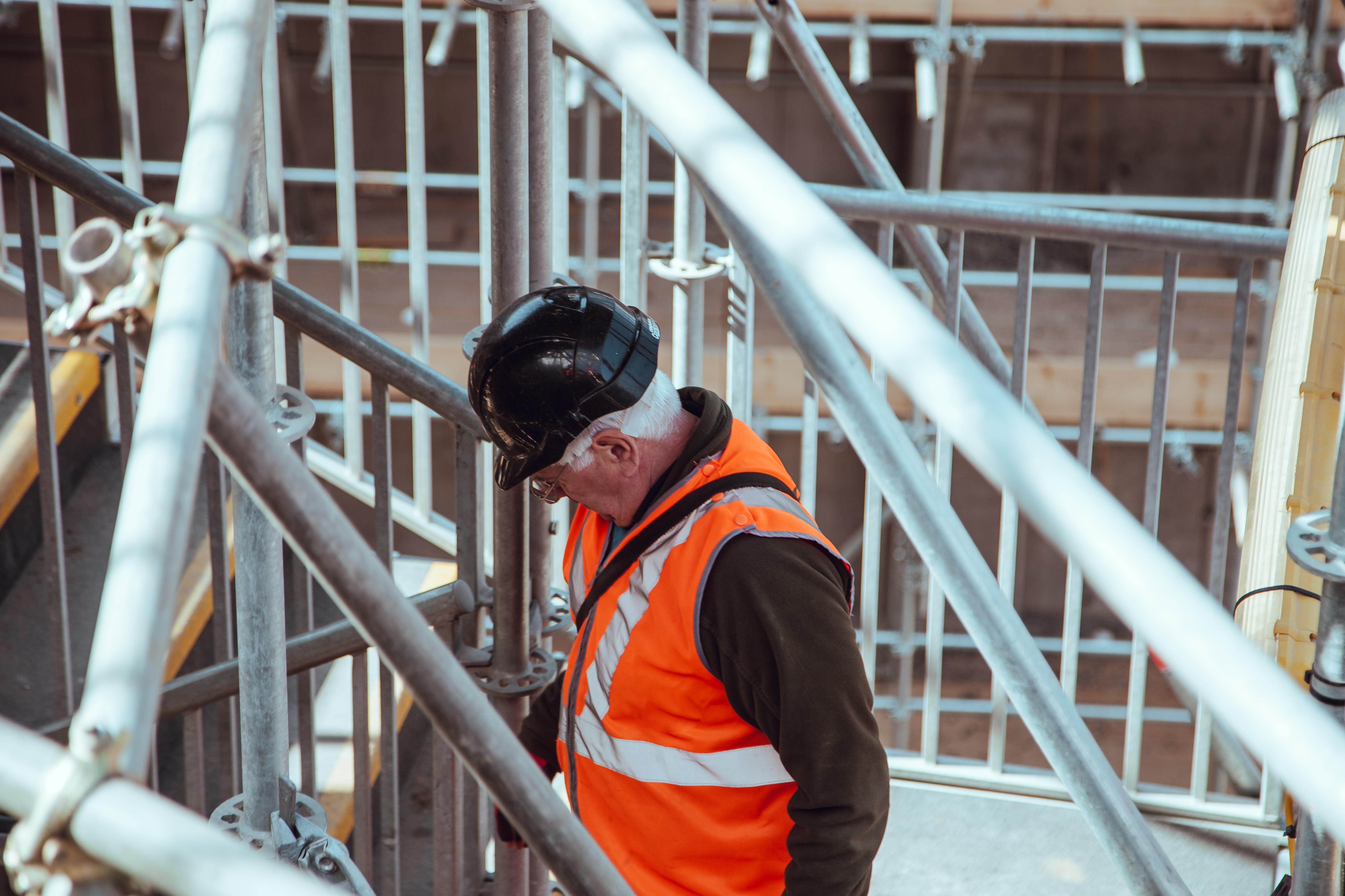 ouvrier sur un chantier portant un casque de sécurité et un gilet