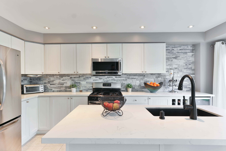 cuisine avec un ilot central blanc et placrds blanc et luminaires dans intégrés au plafond